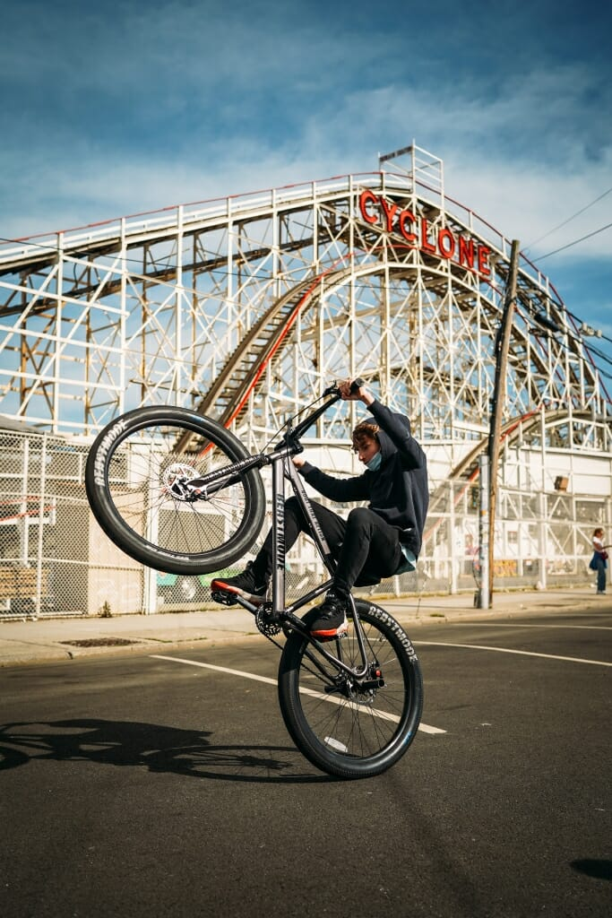 A bicyclist rides in front of Coney Island's Cyclone.